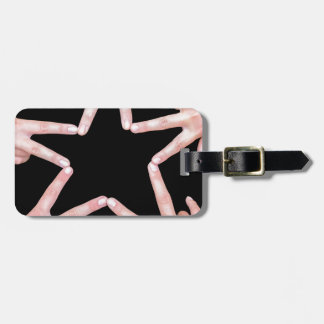 Hands of girls making star shape on black luggage tag
