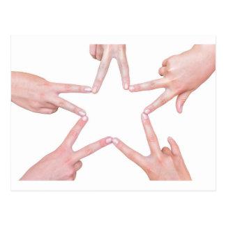 Hands of girls making star shape on white postcard