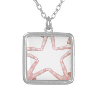 Hands of girls making star shape on white silver plated necklace