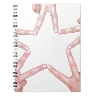 Hands of girls making star shape on white spiral notebooks