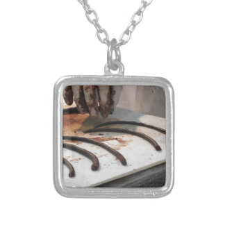 Hands preparing chocolate decoration on a worktop silver plated necklace