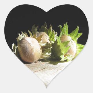 Hazelnuts on the table illuminated by the sunshine heart sticker