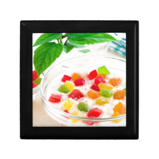 Healthy oatmeal close-up with candied fruit small square gift box