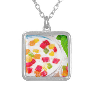 Healthy oatmeal close-up with colorful candied silver plated necklace