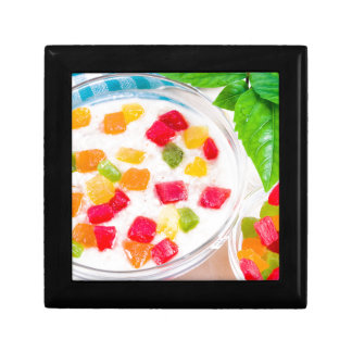 Healthy oatmeal close-up with colorful candied small square gift box