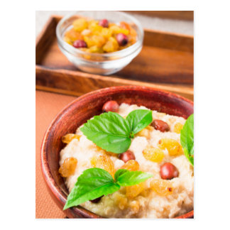 Healthy oatmeal with berries, raisins and herbs postcard