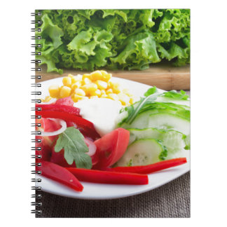 Healthy vegetarian dish on a gray textured fabric spiral notebook