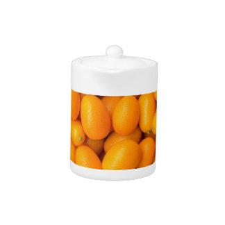 Heap of orange kumquats in cardboard box