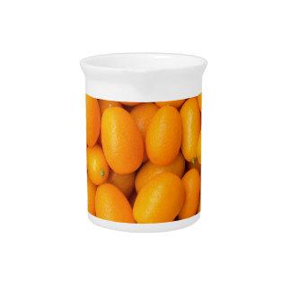 Heap of orange kumquats in cardboard box beverage pitchers