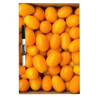 Heap of orange kumquats in cardboard box dry erase board