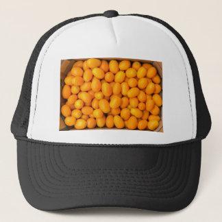 Heap of orange kumquats in cardboard box trucker hat