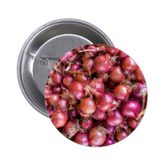 Heap of red onions on market 6 cm round badge