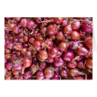 Heap of red onions on market card