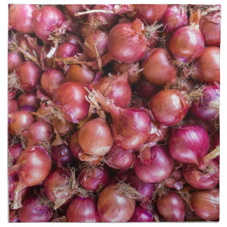 Heap of red onions on market cloth napkin