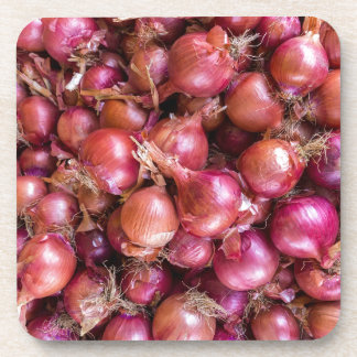 Heap of red onions on market coaster