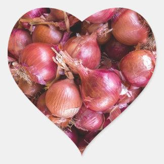 Heap of red onions on market heart sticker