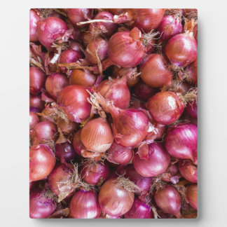 Heap of red onions on market plaque
