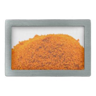 Heap of spice cayenne pepper powder on white belt buckle