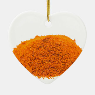 Heap of spice cayenne pepper powder on white ceramic ornament