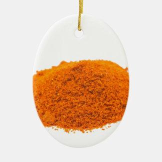 Heap of spice cayenne pepper powder on white ceramic ornament