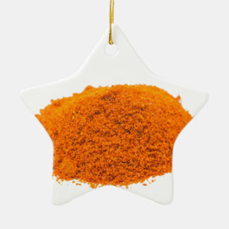Heap of spice cayenne pepper powder on white ceramic star decoration