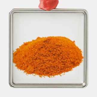 Heap of spice cayenne pepper powder on white metal ornament