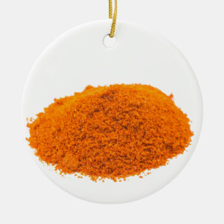 Heap of spice cayenne pepper powder on white round ceramic decoration