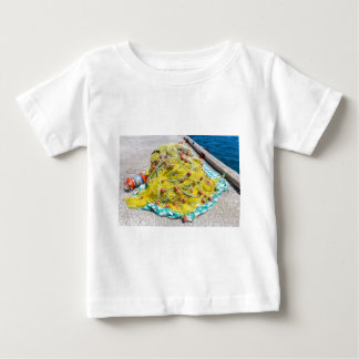 Heap of yellow fishnet on ground at sea baby T-Shirt