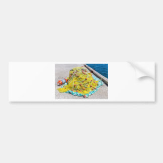 Heap of yellow fishnet on ground at sea bumper sticker