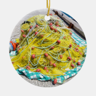 Heap of yellow fishnet on ground at sea ceramic ornament