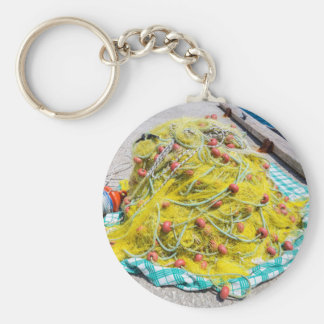 Heap of yellow fishnet on ground at sea key ring