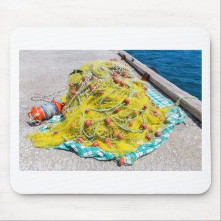 Heap of yellow fishnet on ground at sea mouse pad