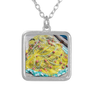 Heap of yellow fishnet on ground at sea silver plated necklace