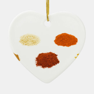 Heaps of several seasoning spices on white ceramic heart decoration