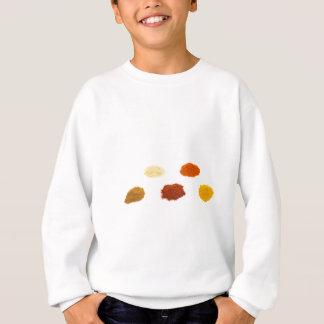 Heaps of several seasoning spices on white sweatshirt
