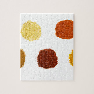 Heaps of various seasoning spices on white jigsaw puzzle