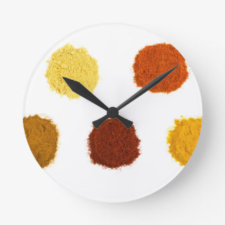 Heaps of various seasoning spices on white wallclocks