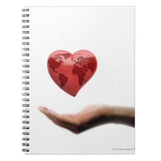 Heart with global map over female hand notebook