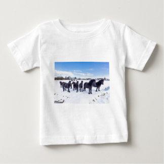 Herd of black frisian horses in winter snow baby T-Shirt