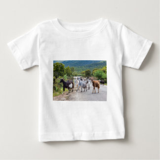 Herd of mountain goats walking on road baby T-Shirt