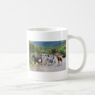 Herd of mountain goats walking on road coffee mug