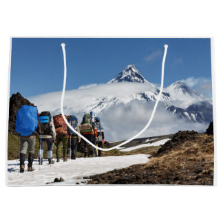 Hikers climbing on mount on background volcanoes large gift bag