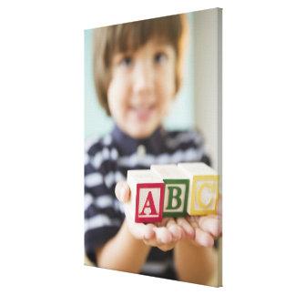 Hispanic boy holding alphabet blocks stretched canvas prints