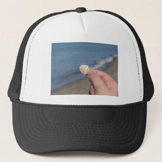 Holding a seashell in the hand trucker hat