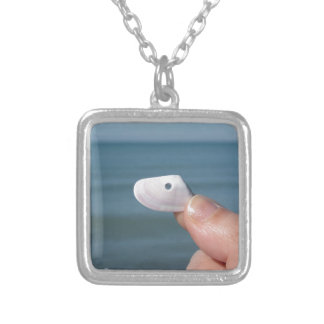 Holding a seashell in the hand with blue sea silver plated necklace