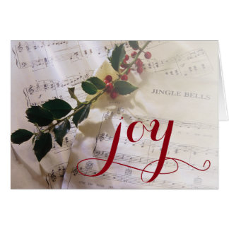 Holly branch on top of sheet music for Christmas Card