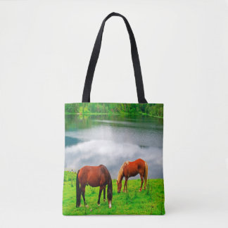 Horses grazing meadow with a forest lake tote bag