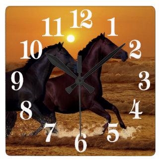 Horses running at ocean sunset square wall clock