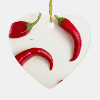 Hot chili peppers on a light wooden board ceramic heart decoration