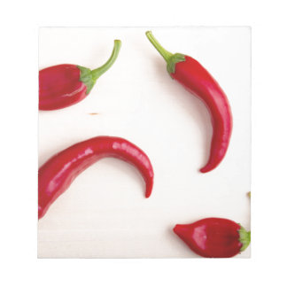 Hot chili peppers on a light wooden board notepads